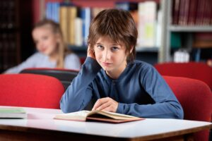 Portrait Of Confused Schoolboy Reading Book In Library